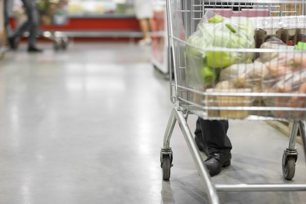Homme marchant avec un chariot entre les rangées de réfrigérateurs. concept de magasinage
