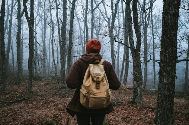 Homme marchant sur un chemin sombre à travers une forêt effrayante. hipster avec un sac à dos dans le dos part en voyage