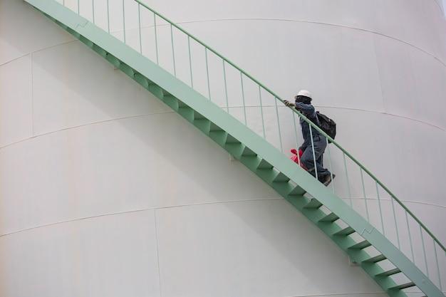 Homme marchant dans l'escalier inspection visuelle du réservoir de stockage chimique.