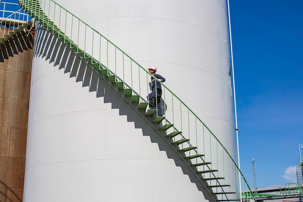 Homme marchant l'huile de réservoir de stockage visuel d'inspection d'escalier