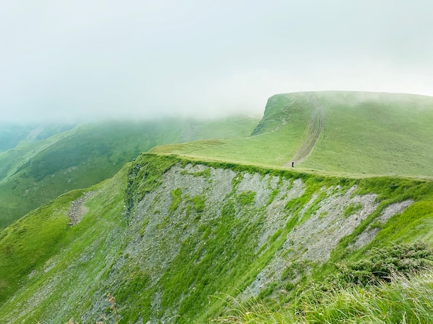 Homme marchant sur la montagne verte avec des nuages en ukraine, carpates, dragobrat