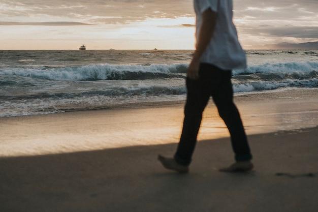 Homme marchant sur la plage au coucher du soleil