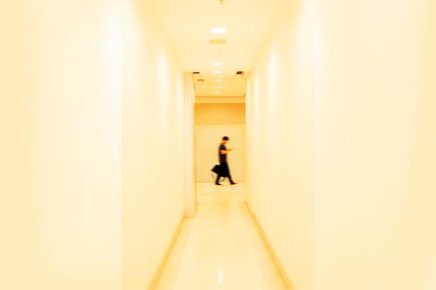 Homme, marche, partie, entre, mur, lumière jaune, à, flou mouvement