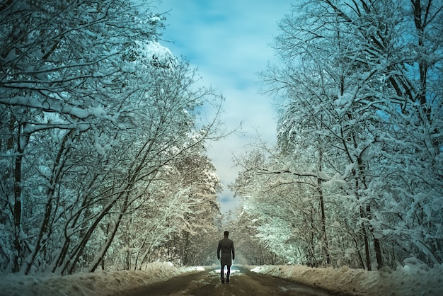 L'homme marche sur la route forestière. le soir la nuit