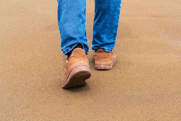 Un homme marche sur le sable