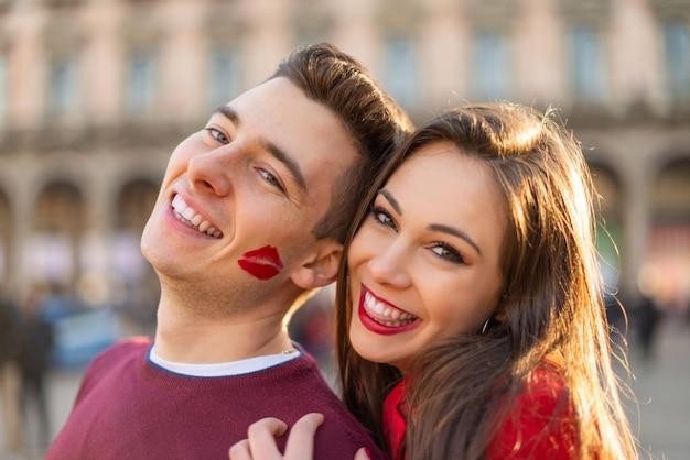 L'homme a une marque de baiser de rouge à lèvres sur sa joue