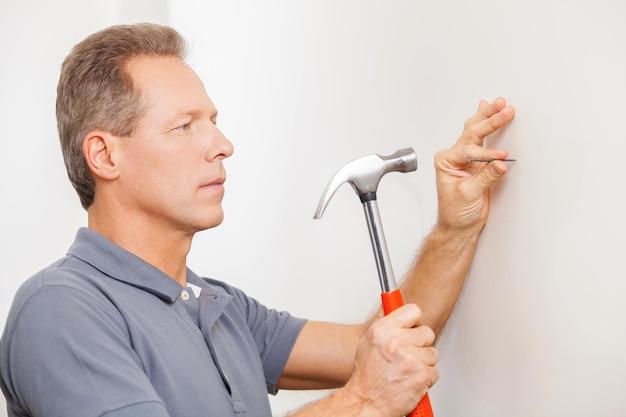 Homme martelant un clou. homme mûr confiant de cheveux gris martelant un clou