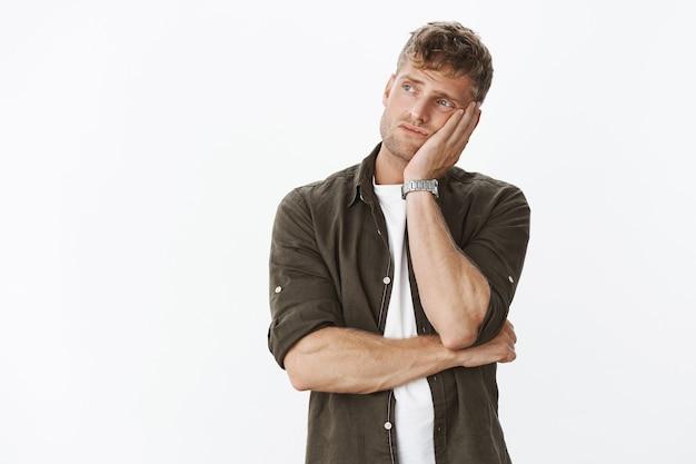 Homme masculin européen mignon triste et solitaire avec barbe et cheveux blonds, tête penchée sur la paume de l'ennui regardant à l'extérieur en tournant à gauche et regardant indifférent avec tristesse sur un mur gris