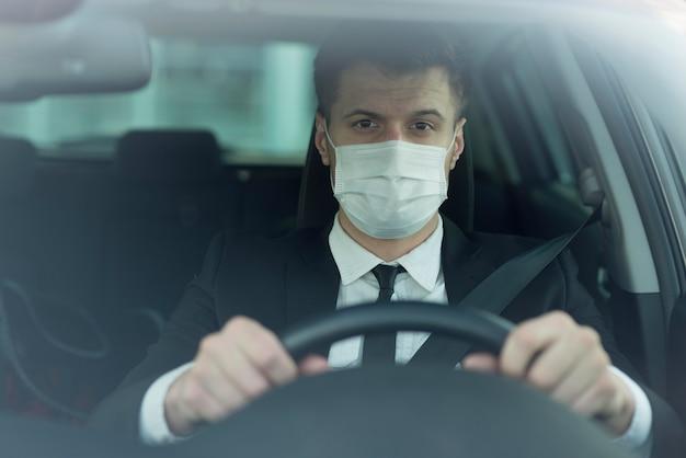 Homme avec masque au volant