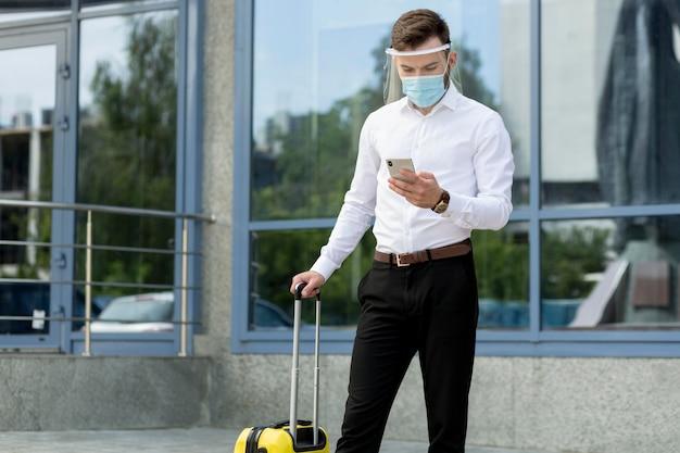 Homme, à, masque, et, bagages, contrôle, téléphone