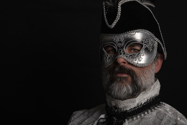 Homme avec masque, chapeau, chemise vénitienne et barbe sur fond noir. concept de carnaval