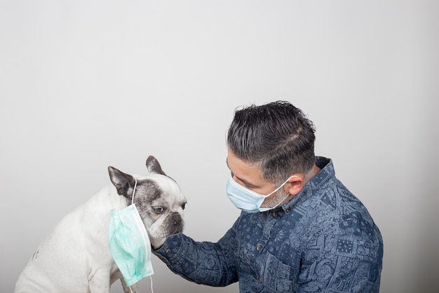 Homme en masque chirurgical protecteur et gants en latex caressant son animal de compagnie. chien bouledogue français