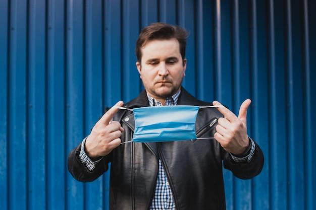 Homme avec masque dans ses mains sur fond bleu, fond, place pour le texte