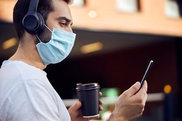 Homme masqué avec du café regardant dans le smartphone
