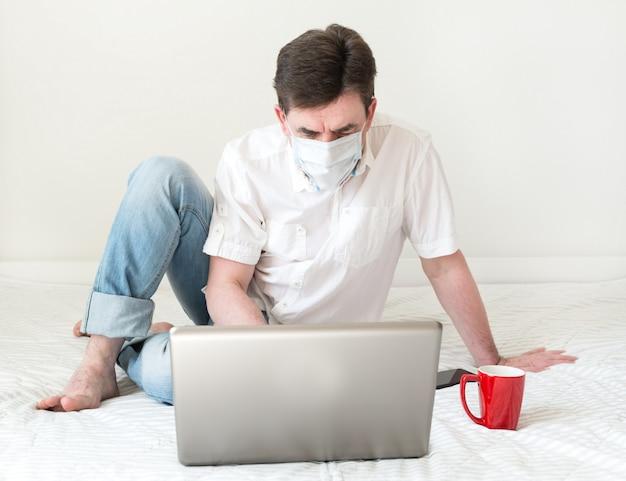 Homme avec un masque facial à l'aide d'un ordinateur portable sur le lit. travail à domicile pendant la quarantaine et l'auto-isolement. concept de coronavirus