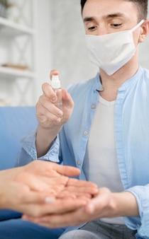 Homme avec masque facial désinfectant les mains