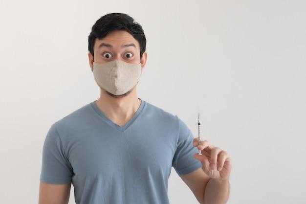 Un homme avec un masque facial injecte un vaccin. concept de protection antivirus.