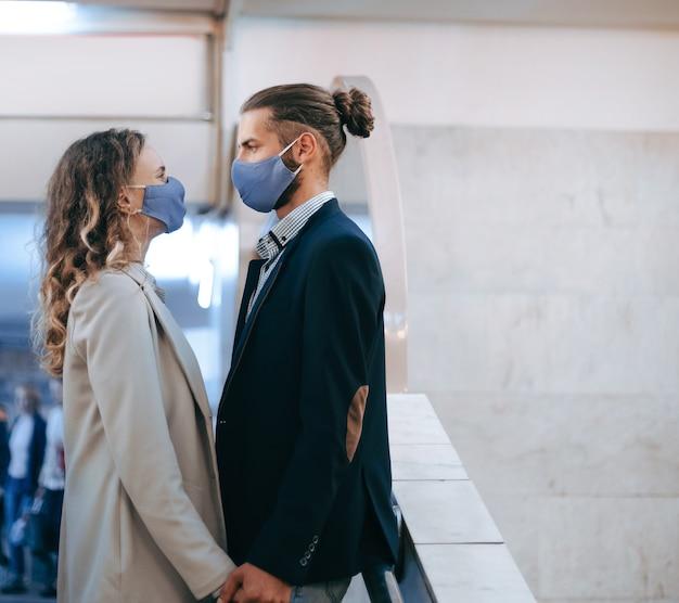Homme masqué et femme amoureuse se tiennent à une station de métro