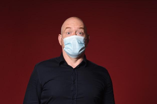 Homme avec masque et gants avec expression surprise du visage sur fond rouge