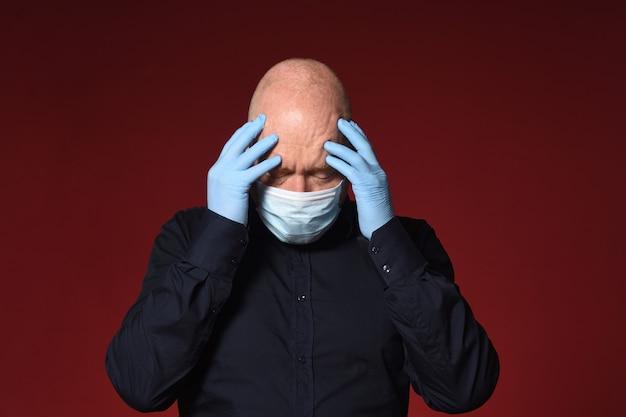 Homme avec masque et gants en latex les mains sur la tête sur fond rouge