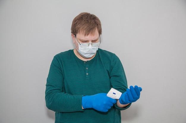 Homme en masque et gants avec un thermomètre contre le coronavirus