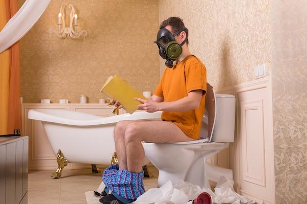 Homme en masque à gaz avec un pantalon assis sur les toilettes et lisant un livre