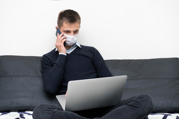 Homme avec masque médical à l'aide d'un ordinateur portable et d'un smartphone