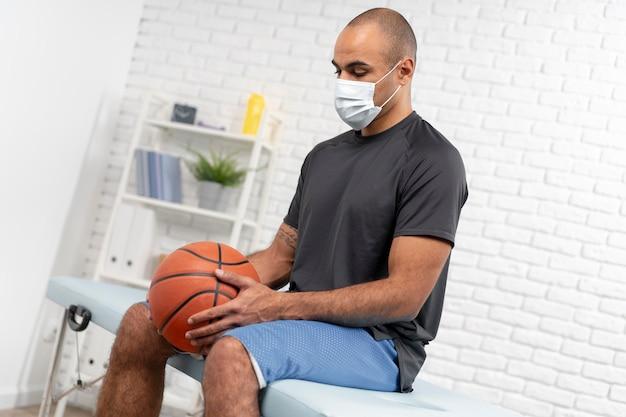 Homme avec masque médical et basket-ball à la physiothérapie