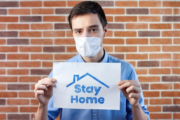 Un homme en masque médical blanc et rester à la maison affiche
