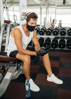 Homme avec masque médical, écouter de la musique sur un casque tout en utilisant un smartphone