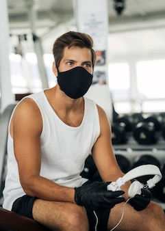 Homme avec masque médical et écouteurs à la salle de sport