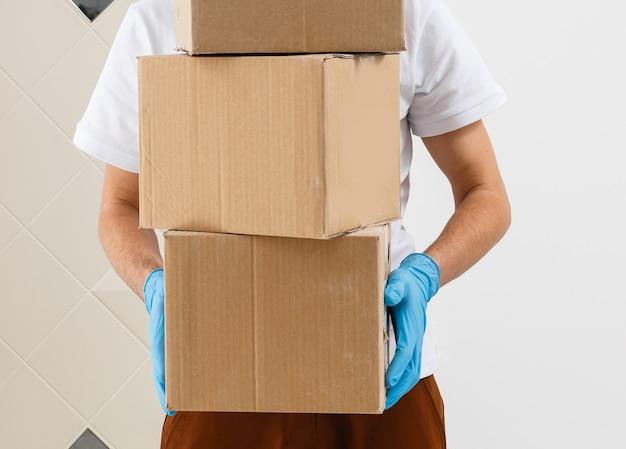 Un homme un masque médical et des gants en caoutchouc bleu avec une boîte, un colis dans les mains. livraison de nourriture pendant la quarantaine de la pandémie de coronavirus. livraison à domicile, commande en ligne. shopping en ligne .