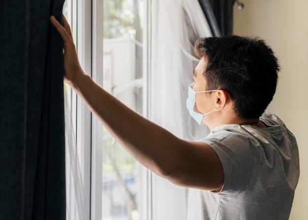 Homme avec masque médical à la maison pendant la pandémie, ouvrant les rideaux de la fenêtre