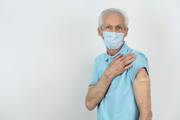 Homme avec masque médical montrant un bandage sur le bras après le vaccin