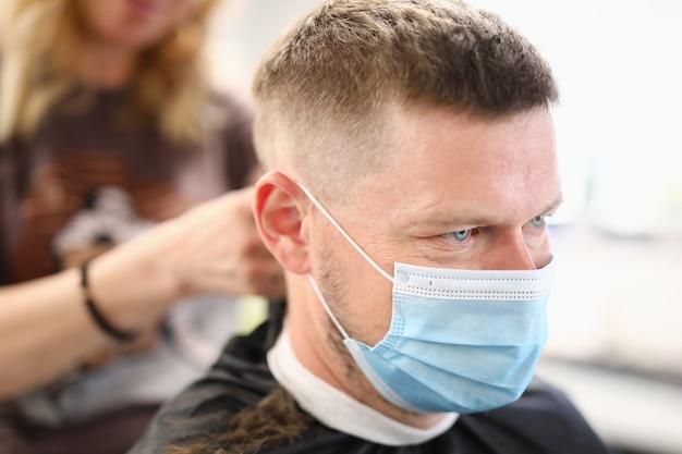 Homme avec masque médical de protection au salon de coiffure