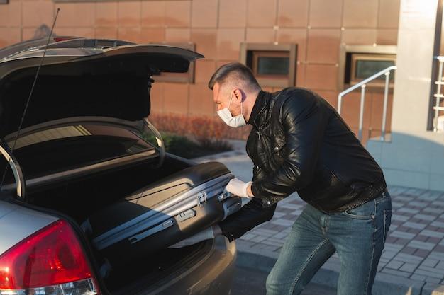Homme en masque médical de protection et gants charger une valise dans le coffre