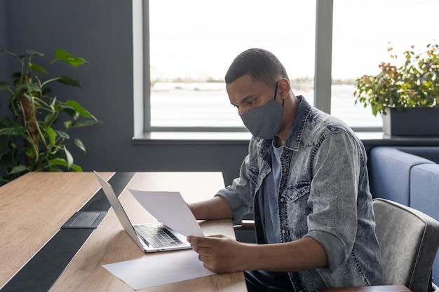 Homme avec masque médical travaillant