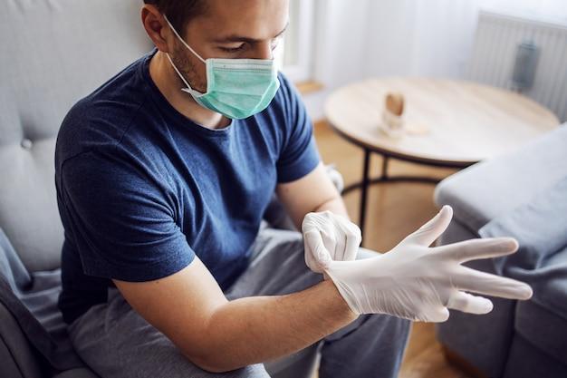Homme avec masque mettant des gants. agir en toute sécurité, se protéger du virus corona.