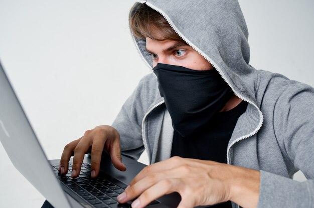 Homme masqué avec ordinateur portable à capuche hacks