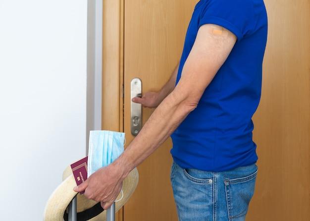 Homme avec masque et passeport ouvrant la porte. valise et chapeau. copie l'espace.