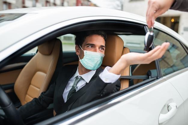 Homme masqué prenant les clés de la voiture
