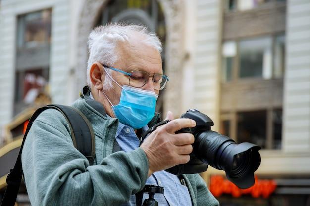 Homme avec masque de prendre une photo par le gratte-ciel de manhattan, new york