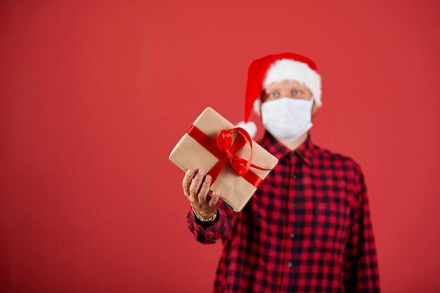 Homme en masque protecteur et bonnet de noel avec cadeau de noël bricolage