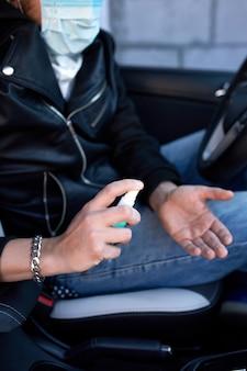 Homme en masque de protection assis dans la voiture, pulvérisation des mains spray désinfectant antibactérien pour la prévention des coronavirus