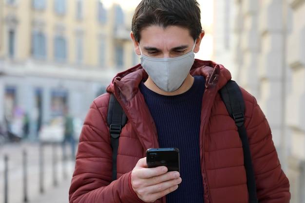 Homme avec masque de protection regarde son smartphone en marchant dans la rue