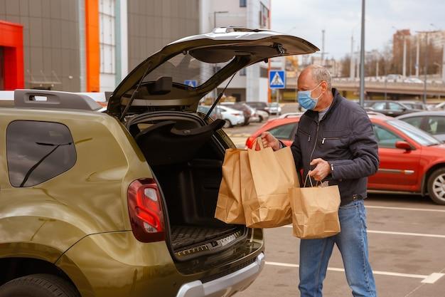 Un homme avec un masque de protection sur le visage charge des paquets de nourriture dans la voiture