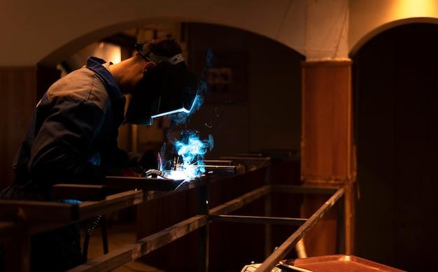 Homme avec masque de soudage métal dans l'atelier