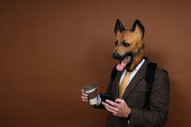 Un homme avec un masque de tête de chien en latex et un sac à dos manipulant un smartphone, portant une tasse de café à la main