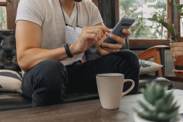 Un homme avec un masque utilise un smartphone et boit du café au café