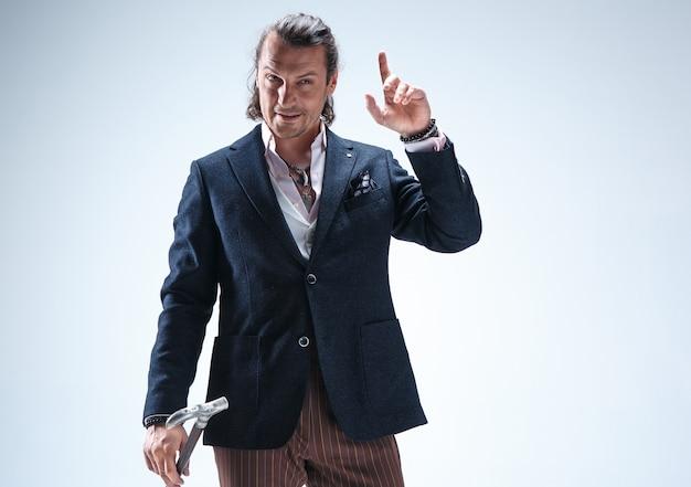 L'homme mature bardé dans un costume tenant la canne.
